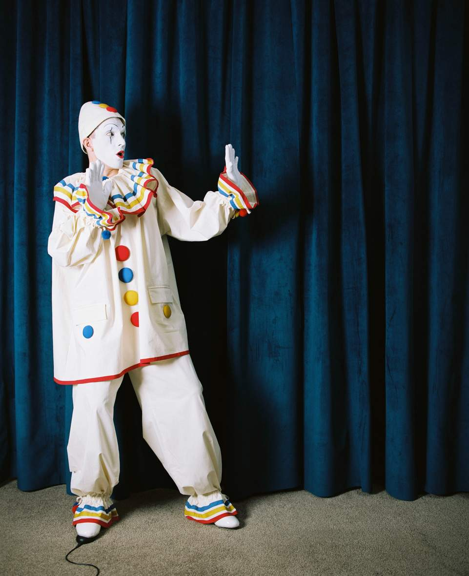The image is a full length shot of a man dressed up as a clown, standing infront of a blue curtain. The man is leaning to the left with his hands up in surprise.