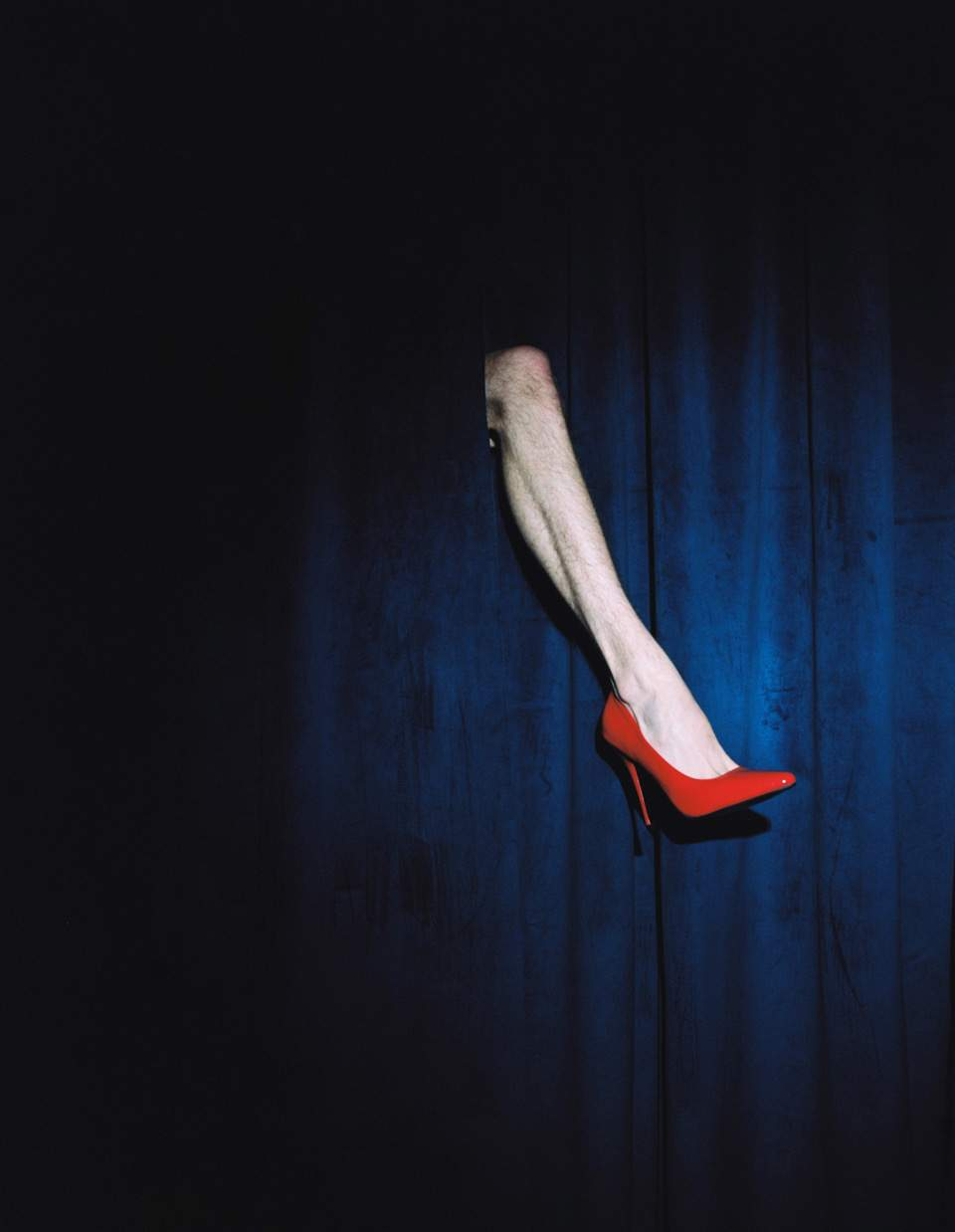 The image is of a leg coming through a blue curtain wearing a red stiletto heel.