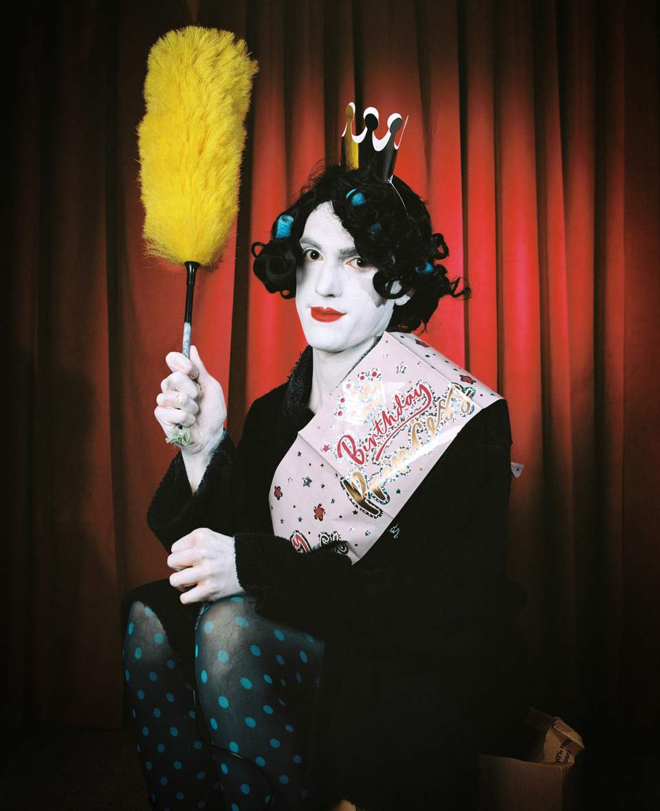The image is a portrait of a man, who is painted white wearing a dark curly wig. They are holding a yellow feather duster in their right hand. Also the man is wearing a dressing gown, blue spotted tights, a pink foil birthday sash and a gold party crown.