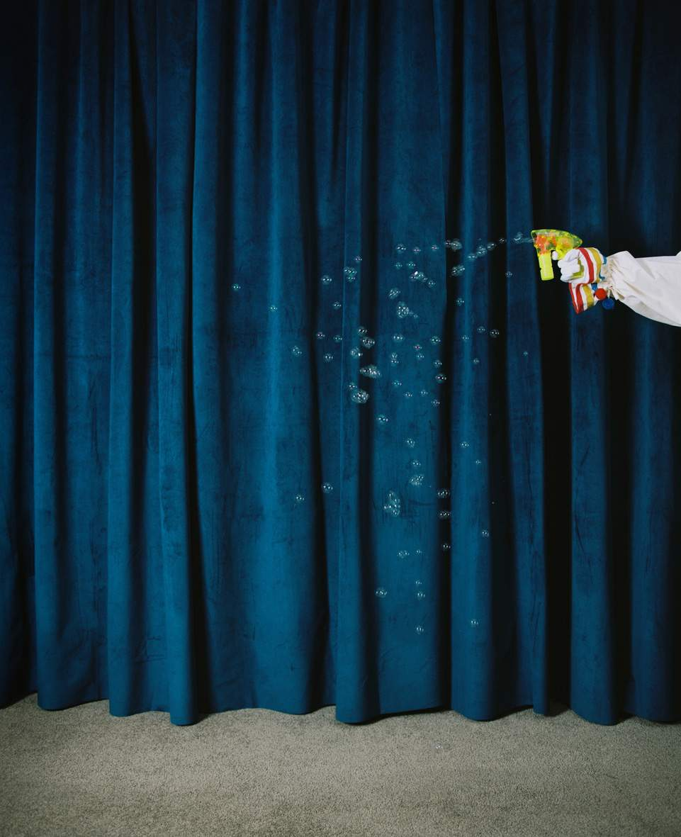 The image is of a blue curtain with a hand holding a bubble gun coming in from the right hand side. There are bubbles floating around in the centre of the image.